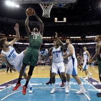 Photo - Milwaukee Bucks forward Ekpe Udoh (13) drives to the basket between New Orleans Hornets center Robin Lopez (15), forward Al-Farouq Aminu (0) and forward Ryan Anderson, right, in the first half of an NBA basketball game in New Orleans, Monday, Dec. 3, 2012. (AP Photo/Gerald Herbert)