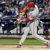 Photo - Philadelphia Phillies' Chase Utley hits a sacrifice fly to score Ben Revere during the first inning of a baseball game against the Ne York Mets, Saturday, May 10, 2014, at Citi Field in New York. (AP Photo/Bill Kostroun)