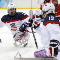 Photo - United States's Joshua Pauls, left, celebrates as Joshua Sweeney, right scores a goal during the gold medal ice sledge hockey match between United States and Russia at the 2014 Winter Paralympics in Sochi, Russia, Saturday, March 15, 2014. (AP Photo/Pavel Golovkin)
