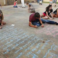 Photo - Students in Dustin Johnson's freshman English classes at Choctaw High School observed National Poetry Month and Poem in Your Pocket Day on Thursday by writing poems in chalk.