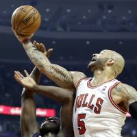 Photo - Chicago Bulls forward Carlos Boozer, right, battles for a rebound with Memphis Grizzlies forward Zach Randolph during the first half of an NBA basketball game in Chicago on Saturday, Jan. 19, 2013. (AP Photo/Nam Y. Huh)