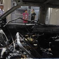 Photo - Civilians inspect the aftermath of a car bomb attack in Baghdad, Iraq, Wednesday, July 24, 2013. A bomb exploded near a Sunni mosque in Baghdad's southern Dora neighborhood on Tuesday, killing four and wounding 12,  police said. (AP Photo/Karim Kadim)