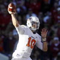 Photo - Oklahoma State quarterback Clint Chelf throws against Oklahoma in the second quarter of an NCAA college football game in Norman, Okla., Saturday, Nov. 24, 2012. (AP Photo/Sue Ogrocki)
