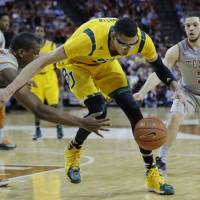 Photo - Baylor's Isaiah Austin, center, is pressured by Texas defenders Jonathan Holmes, left, and Javan Felix (3) during the second half of an NCAA college basketball game, Wednesday, Feb. 26, 2014, in Austin, Texas. Texas won 74-69. (AP Photo/Eric Gay)