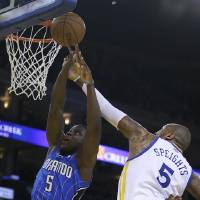 Photo - Orlando Magic's Victor Oladipo, left, lays up a shot against Golden State Warriors' Marreese Speights during the first half of an NBA basketball game Tuesday, March 18, 2014, in Oakland, Calif. (AP Photo/Ben Margot)