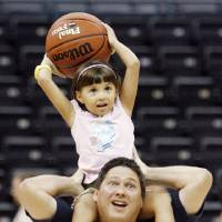 Photo - Risa Slepikas, 5, shoots a basket on the shoulders of her father, Mark Slepikas during the All Access Tour of the Ford Center in Oklahoma City, Saturday, July 12, 2008. BY NATE BILLINGS, THE OKLAHOMAN ORG XMIT: KOD