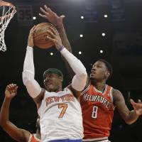 Photo - Milwaukee Bucks' Larry Sanders (8) defends against New York Knicks' Carmelo Anthony (7) during the first half of an NBA basketball game on Friday, April 5, 2013, in New York. (AP Photo/Frank Franklin II)