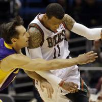 Photo - Los Angeles Lakers' Steve Nash, left, reaches in on Milwaukee Bucks' Monta Ellis during the second half of an NBA basketball game, Thursday, March 28, 2013, in Milwaukee. (AP Photo/Jeffrey Phelps)