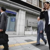 Photo -   People walk past a digital display of Tokyo stock prices at a securities firm in Tokyo Monday, July 2, 2012. Asian stock markets inched higher Monday amid continued optimism over Europe's moves to ease its debt crisis and economic malaise. (AP Photo/Koji Sasahara)