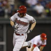 Photo - Arizona Diamondbacks' Nick Evans, left, rounds the bases past Philadelphia Phillies second baseman Chase Utley after hitting a three-run home run during the 10th inning of a baseball game, Saturday, July 26, 2014, in Philadelphia. Arizona won 10-6 in 10 innings. (AP Photo/Matt Slocum)