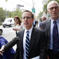 Photo - Carmine Boccuzzi, center, a lawyer representing Argentina, leaves federal court after a hearing regarding the country's request to extend deadlines to repay a $1.65 billion debt to U.S. hedge funds, Friday, June 27, 2014, in New York.   Judge Thomas P. Griesa has ordered a U.S. bank to return a $539 million payment from Argentina, saying it was illegal to make. The order by the judge came Friday, three days before Argentina faces default if it fails to pay $832 million to the majority of its debt holders. (AP Photo/Jason DeCrow)