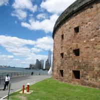 Photo - This June 6, 2014 photo shows Castle Williams, a 19th century fort located on Governors Island in New York City, with a view of 1 World Trade Center and Lower Manhattan in the distance. Castle Williams was used as barracks and  a prison on the island, which is a former military and Coast Guard facility. Now a national park site, the island is open daily to visitors through the summer. It's dotted with green lawns, outdoor art and historic buildings and it offers a variety of events and activities, along with scenic views of Manhattan. (AP Photo/Beth J. Harpaz)