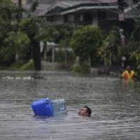Photo -   A man crosses deep floodwaters using water containers as floaters in suburban Quezon City, north of Manila, Philippines on Tuesday Aug. 7, 2012. Torrential rains pounding the Philippine capital on Tuesday paralyzed traffic as waist-deep floods triggered evacuations of tens of thousands of residents and the government suspended work in offices and schools.(AP Photo/Aaron Favila)