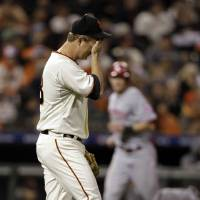 Photo -   San Francisco Giants pitcher Matt Cain reacts after giving up a two-run home home to Cincinnati Reds' Brandon Phillips in the third inning of Game 1 of the National League division baseball series in San Francisco, Saturday, Oct. 6, 2012. (AP Photo/Eric Risberg)