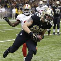 Photo - New Orleans Saints tight end Josh Hill (89) scores on a touchdown reception in front of San Francisco 49ers strong safety Donte Whitner in the first half of an NFL football game in New Orleans, Sunday, Nov. 17, 2013. (AP Photo/Bill Haber)