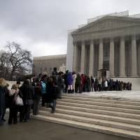 Photo - People wait in line outside the Supreme Court in Washington, Wednesday, Feb. 27,2013, to listen to oral arguments in the Shelby County, Ala., v. Holder voting rights case. The justices are hearing arguments in a challenge to the part of the Voting Rights Act that forces places with a history of discrimination, mainly in the Deep South, to get approval before they make any change in the way elections are held. (AP Photo/Evan Vucci)