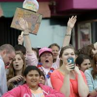 Photo - Peg Allen, of Franklinville, N.J., with arms raised, watches a live performance by musical group Fun at the Seaside Heights boardwalk, Friday, May 24, 2013, in Seaside Heights, N.J. New Jersey Gov. Chris Christie cut a ribbon to symbolically reopen the state's shore for the summer season, seven months after being devastated by Superstorm Sandy. Several beach communities have annual beach ribbon cuttings, announcing they are back in business. But this year's ceremonies are more poignant seven months after a storm that did an estimated $37 billion of damage in the state. (AP Photo/Julio Cortez)