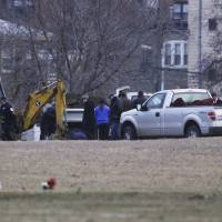 Photo - A backhoe is seen at Rosehill Cemetery in Chicago, Friday, Jan. 18, 2013, as workers begin the process of exhuming the body of Urooj Khan who was poisoned with cyanide after winning the lottery. Khan died in July as he was about to collect $425,000 in lottery winnings. His death was initially ruled a result of natural causes, but a relative pressed for a deeper look and his death was reclassified as a homicide.  (AP Photo/M. Spencer Green)