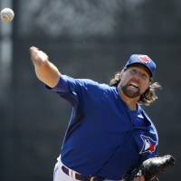 Photo - Toronto Blue Jays starting pitcher R.A. Dickey delivers a warmup pitch before starting in a spring training baseball game against the New York Yankees in Dunedin, Fla., Wednesday, March 26, 2014.  (AP Photo/Kathy Willens)