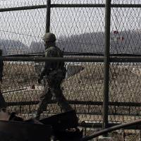 Photo - South Korean army soldiers patrol along a barbed-wire fence at the Imjingak Pavilion near the border village of Panmunjom, which has separated the two Koreas since the Korean War, in Paju, north of Seoul, South Korea, Friday, March 15, 2013. The Koreas' border can seem a surreal place at the best of times — part tourist trap, part war zone. An amusement park, fast-food joints and kitschy souvenir shops mix with an ever-present Cold War tension that is higher now than it has been in years, following North Korean outrage over U.N. sanctions and joint U.S.-South Korean military drills.(AP Photo/Lee Jin-man)