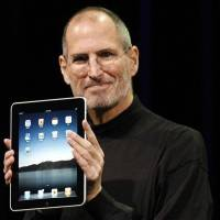 Photo - Apple CEO Steve Jobs shows off the new iPad during an event in San Francisco, Wednesday, Jan. 27, 2010. (AP Photo/Paul Sakuma)