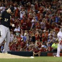 Photo - Pittsburgh Pirates relief pitcher Justin Wilson, left, stands on the mound as St. Louis Cardinals' Kolten Wong rounds the bases after hitting a solo home run during the seventh inning of a baseball game Wednesday, July 9, 2014, in St. Louis. (AP Photo/Jeff Roberson)