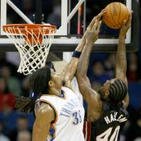Photo - Oklahoma City's Etan Thomas blocks the shot of Miami's Udonis Haslem during a preseason NBA basketball game between the Oklahoma City Thunder and the Miami Heat at the BOK Center in Tulsa, Okla., Wednesday, October 14, 2009. Photo by Bryan Terry, The Oklahoman ORG XMIT: KOD