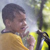 Photo - FILE - This July 6, 2012 file photo shows six-year-old Alexander Merrill of Sioux Falls, S.D., cooling off in a cloud of mist at the Henry Doorly Zoo in Omaha, Neb., as temperatures reached triple digits. Federal meteorologists say America was deep fried in 2012, becoming the hottest year on record by far. The National Climatic Data Center in Ashville, N.C., calculates that the average U.S. temperature in 2012 was 55.32 degrees Fahrenheit. That's a full degree warmer than the previous record of 1998. Normally, records are broken by about a tenth of a degree. (AP Photo/Nati Harnik, File)