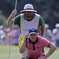 Photo - Martin Kaymer, bottom, of Germany, and his caddie Craig Connelly look at Kaymer's shot on the seventh green during the final round of The Players championship golf tournament at TPC Sawgrass, Sunday, May 11, 2014, in Ponte Vedra Beach, Fla. (AP Photo/Lynne Sladky)