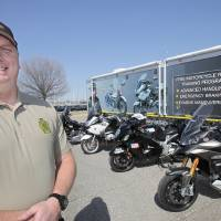 Photo - Oklahoma Highway Patrol Trooper Clint Riddle with the advanced motorcycle training equipment used to teach riders statewide. Photo by David McDaniel, The Oklahoman
