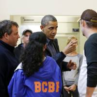 Photo -   President Barack Obama, accompanied by New Jersey Gov. Chris Christie meets with local residents at the Brigantine Beach Community Center in Brigantine, NJ., Wednesday, Oct. 31, 2012. Obama traveled to Atlantic Coast to see first-hand the relief efforts after Superstorm Sandy damage the Atlantic Coast. (AP Photo/Pablo Martinez Monsivais)