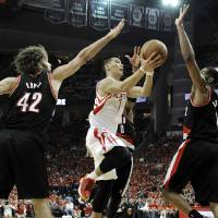 Photo - Houston Rockets' Jeremy Lin (7) goes to the basket between Portland Trail Blazers Robin Lopez (42) and LaMarcus Aldridge in the second half of Game 5 of an opening-round NBA basketball playoff series Wednesday, April 30, 2014, in Houston. The Rockets won 108-98 to send the teams back to Portland for Game 6. (AP Photo/Pat Sullivan)