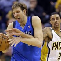 Photo - Indiana Pacers guard George Hill, right, reaches around Dallas Mavericks forward Dirk Nowitzki during the second half of an NBA basketball game in Indianapolis, Wednesday, Feb. 12, 2014. The Mavericks defeated the Pacers 81-73. (AP Photo/Michael Conroy)