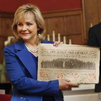 Photo - Gov. Mary Fallin holds up a Sunday, April 20, 1913, newspaper just removed from the Century Chest at First Lutheran Church in Oklahoma City Monday, April 22, 2013. The Century Chest is a time capsule put together and buried April 22, 1913 by the church. Photo by Paul B. Southerland, The Oklahoman