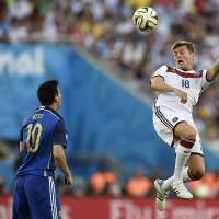 Photo - Germany's Toni Kroos (18) rises above Argentina's Lionel Messi (10) to head the ball during the World Cup final soccer match between Germany and Argentina at the Maracana Stadium in Rio de Janeiro, Brazil, Sunday, July 13, 2014. (AP Photo/Martin Meissner)