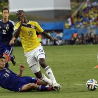 Photo - Japan's Yasuyuki Konno fouls Colombia's Adrian Ramos to give away a penalty during the group C World Cup soccer match between Japan and Colombia at the Arena Pantanal in Cuiaba, Brazil, Tuesday, June 24, 2014. (AP Photo/Thanassis Stavrakis)