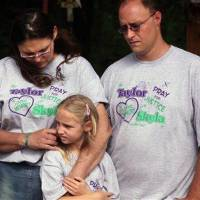 Photo - From left, Rose Whitaker, Jayme Whitaker, 8, and William Whitaker comfort each other during a news conference held at the site where their daughter, Skyla Jade Whitaker, 11, and her friend, Taylor Paschal-Placker, 13, were killed on a country road just north of Weleetka, Okla., Tuesday, June 8, 2010. The girls were found shot to death on June 8, 2008, along a dirt road near Weleetka. (AP Photo/Tulsa World, Adam Wisneski)