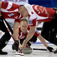 Photo - FILE  In this April 6, 2013, file photo, Canada skip Brad Jacobs, center, makes a shot as second, E.J. Harnden, right, and lead Ryan Harnden sweep during a page 3-4 playoff draw against Denmark at the World Men's Curling Championship in Victoria, British Columbia. After a breakthrough year in 2013 in which his rink became Canadian champion before romping through Olympic trials, Jacobs heads to the Sochi Games as the big favorite for the gold medal.  (AP Photo/The Canadian Press, Jonathan Hayward, File)