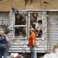 Photo - Residents of Steelman Estates in Bethel Acres sift through the remains of their homes on Monday, May 20, 2013, after a violent tornado ripped through the neighborhood yesterday, killing one man.    Photo  by Jim Beckel, The Oklahoman.