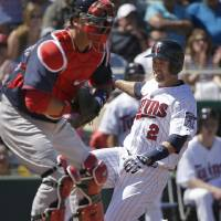 Photo - Minnesota Twins' Brian Dozierin, right, scores on an RBI single by Joe Mauer as Boston Red Sox catcher A.J. Pierzynski, left, tries to make the play in the first inning of an exhibition baseball game, Saturday, March 1, 2014, in Fort Myers, Fla. (AP Photo/Steven Senne)