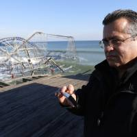 Photo - New Jersey State Assemblyman Angel Fuentes stands on the Funtown Pier at Seaside Heights as a roller coaster is dunked in the ocean during a tour of the areas hit by Superstorm Sandy, Thursday, Nov. 29, 2012, in Seaside Heights, N.J. (AP Photo/Julio Cortez)