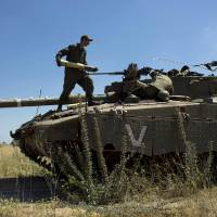 Photo - Israeli soldiers load shells in their tank following the first death on the Israeli side of the Golan since the Syrian civil war erupted more than three years ago, near the Israeli village of Alonei Habashan, in the area of Tel Hazeka, close to the Quneitra border crossing in the Israeli-controlled Golan Heights, Sunday, June 22, 2014. A civilian vehicle in the Golan Heights was targeted by forces in neighboring Syria on Sunday in an attack that killed a 15-year-old boy and prompted Israeli tanks to retaliate by firing on Syrian government targets, the Israeli military said. (AP Photo/Oded Balilty)