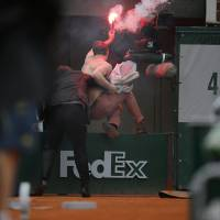 Photo - A security guard removes a demonstrator who ran onto center court as Spain's Rafael Nadal plays against compatriot David Ferrer in the final of the French Open tennis tournament, at Roland Garros stadium in Paris, Sunday June 9, 2013. (AP Photo/Michel Spingler)