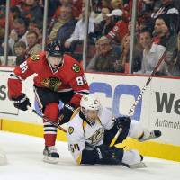 Photo - Chicago Blackhawks' Patrick Kane (88) and Nashville Predators' Victor Bartley (64) collide during the second period of an NHL hockey game Friday, April 19, 2013, in Chicago. (AP Photo/Jim Prisching)