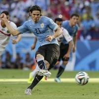 Photo - Uruguay's Edinson Cavani (21) kicks a penalty shot to score his side's first goal during the group D World Cup soccer match between Uruguay and Costa Rica at the Arena Castelao in Fortaleza, Brazil, Saturday, June 14, 2014.  (AP Photo/Fernando Llano)