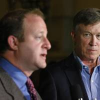 Photo - Colo. Gov. John Hickenlooper, right, listens as U.S. Rep. Jared Polis, D-Colo., takes questions during a news conference about fracking, at the Capitol, in Denver, Monday, Aug. 4, 2014. During the news conference Hickenlooper announced the creation of a task force charged with crafting recommendations to help minimize land use conflicts that can occur when siting oil and gas facilities near homes, schools, businesses and recreational areas. (AP Photo/Brennan Linsley)