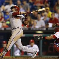 Photo - Arizona Diamondbacks' Martin Prado, left, follows through after hitting a go-ahead RBI-sacrifice fly off Philadelphia Phillies relief pitcher Antonio Bastardo during the 10th inning of a baseball game on Saturday, July 26, 2014, in Philadelphia. Phillies catcher Carlos Ruiz, right, looks on. Arizona won 10-6 in 10 innings. (AP Photo/Matt Slocum)