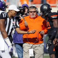 Photo - Radio broadcaster Robert Allen records the coin flip before a college football game between Oklahoma State University (OSU) and Texas Christian University (TCU) at Boone Pickens Stadium in Stillwater, Okla., Saturday, Oct. 27, 2012. Photo by Nate Billings, The Oklahoman