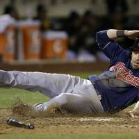 Photo - Cleveland Indians' Jason Kipnis scores on a groundout by Michael Brantley against the Oakland Athletics during the seventh inning of a baseball game in Oakland, Calif., Wednesday, April 2, 2014. (AP Photo/Jeff Chiu)