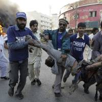 Photo - Pakistani volunteers carry a wounded bus passenger following a blast in Karachi, Pakistan on Saturday, Dec. 29, 2012. The blast that ripped through the bus  set the vehicle on fire and reduced it to little more than a charred skeleton, killing scores of people and left many injured. Police were trying to determine whether the explosion was caused by a bomb or a gas cylinder, said police spokesman. Many buses in Pakistan run on natural gas. (AP Photo/Fareed Khan)